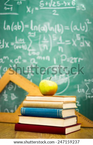 apple on stack of books with math formulas written on chalkboard  - stock photo
