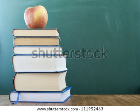 Apple on the books. Blank chalkboard in the background, space for text and graphics. - stock photo
