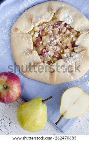 Apple pear galette. A galette is a rustic, free-form tart that is cooked on a baking sheet and can be prepared with a variety of seasonal fruits. - stock photo