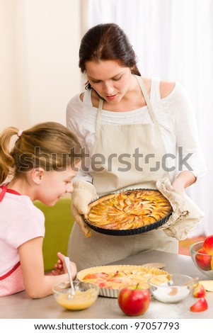 Apple pie mother and daughter baking together happy at home - stock photo