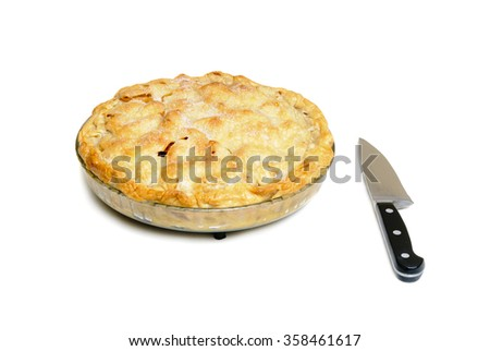 Apple pie with a knife on a white background - stock photo