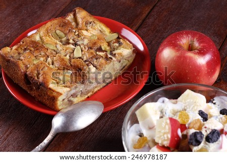 Apple pie with seeds on a plate. Fruit salad with yogurt and cake on the table. Apple pie, plate and spoon. Hearty and delicious dessert. Homemade cakes. - stock photo