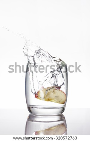 Apple pieces drop into a glass of water, make water splashing, on white background - stock photo