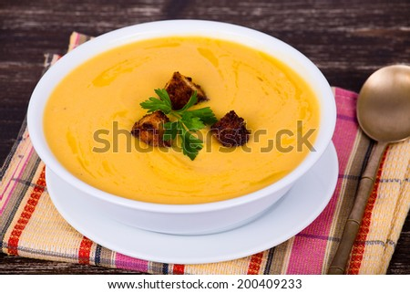 Apple pumpkin cream soup in a dish - stock photo