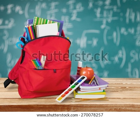 Apple. Purple backpack with school supplies isolated on white - stock photo