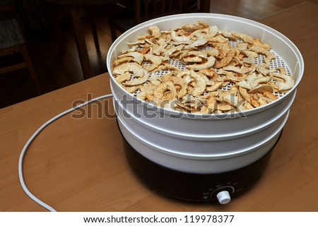 Apple slices drying in a dessicator. Space for text top left. - stock photo