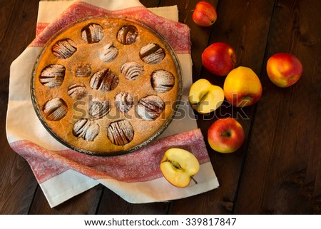 Apple tasty traditional homemade delicious breakfast baking pie tart sweet dessert in a glass baking dish, and apples on dark background, top view. Pastry. Dessert. Apple Pie. Apple Tart. Pie. Tart   - stock photo