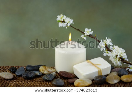 apple tree blossoms with stones candle on mat - stock photo