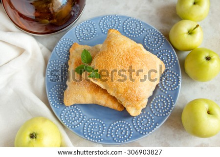 apple turnovers on blue plate with raw apple, top view - stock photo