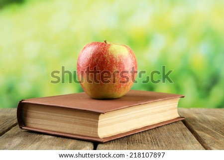 Apple with book on table on bright background - stock photo