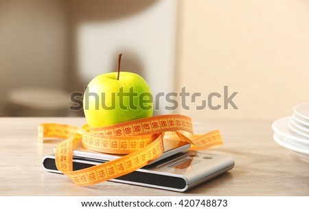 Apple with centimeter and digital kitchen scales on wooden table - stock photo