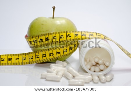 Apple with measuring tape and pills - stock photo