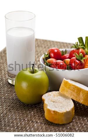 Apple with Vegetables Bread and Glass of Milk on Placemat - stock photo