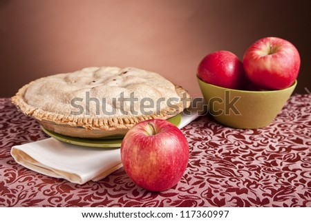 Apples and a freshly baked apple pie. - stock photo