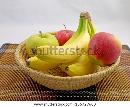 Apples and bananas in a basket. - stock photo