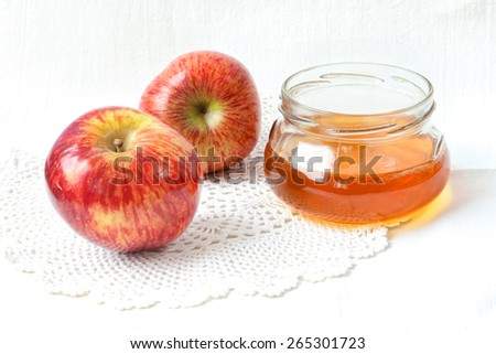 Apples and honey in a glass pot on a white linen cloth  - stock photo