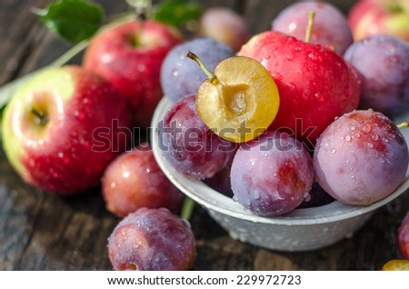 apples and plums on a wooden table - stock photo