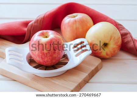 Apples and slicer on a wood background. - stock photo