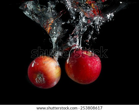 Apples are falling into the water with a splash and air bubbles on a black background. Tasty and healthy food. Wash fruits. - stock photo