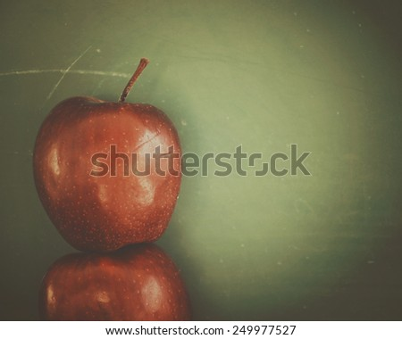 Apples are in front of a textured green school chalkboard with blank copyspace to add your education message. - stock photo
