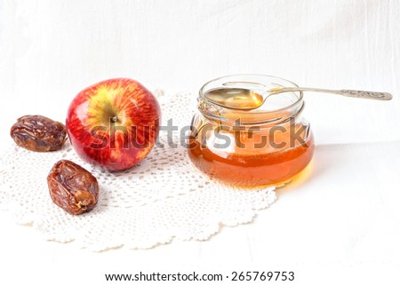 Apples, dates  and honey in a glass pot on a linen cloth - stock photo