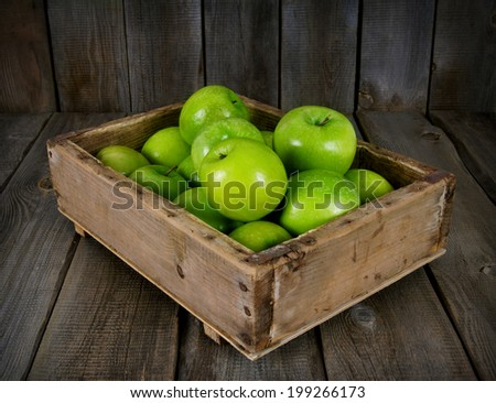 Apples in an old box, on a wooden background. - stock photo