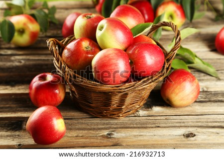 Apples in basket on brown wooden background - stock photo