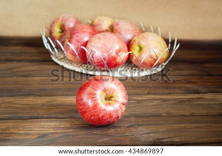 Apples in wicker basket on old wooden background - stock photo