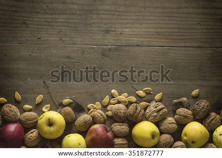 Apples, nut and seed mix on rustic wooden table with place for your text - stock photo