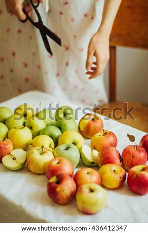 Apples  on white table. Sweet apples on table on bright background. basket with ripe tasty apples on white table. White table full of freshly harvested red apples with a halved apple on display  - stock photo
