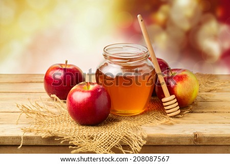 Apples with honey jar on wooden table over bokeh background - stock photo