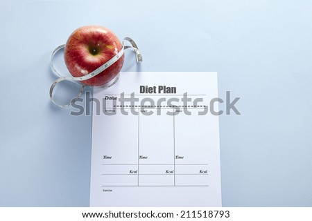 Apples with measuring tape and diet Plan - stock photo