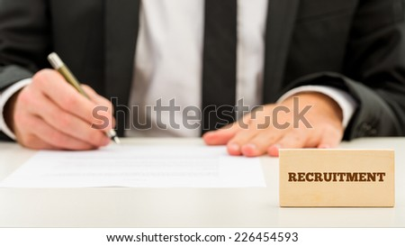 Applicant completing a job application with a small wooden block in the foreground with the word - recruitment - focus to the block. - stock photo