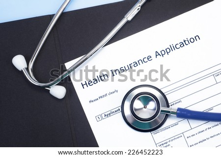 Application for health insurance with stethoscope. - stock photo