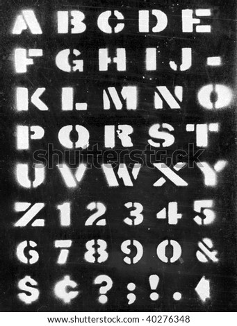 Applied paint with stencil alphabet on black - stock photo