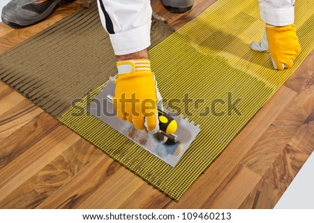 applies tile adhesive on wooden floor with reinforce fiber mesh - stock photo