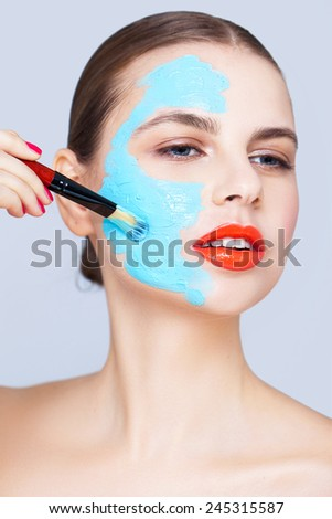 Applying blue clay mask - stock photo