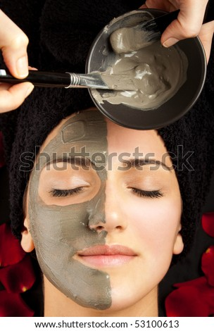 applying clay mask on young woman's face, half covered - stock photo