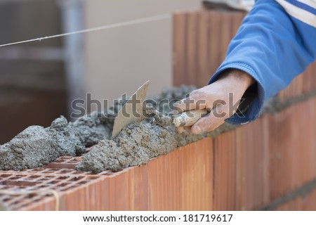 Applying construction trowel on brick wall , builder working on construction site  - stock photo