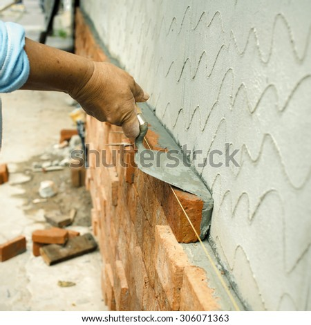 Applying construction trowel with brick wall - stock photo