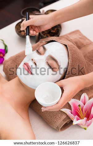 Applying facial mask on a female face - stock photo