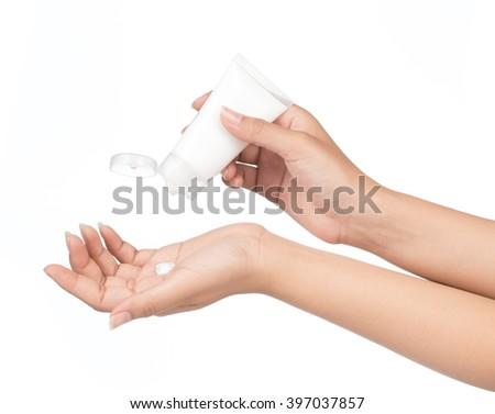 Applying hand moisturizer cream on female hands isolated on white background - stock photo