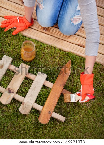 Applying protective varnish to a wooden fence  - stock photo