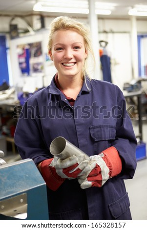 Apprentice Engineer Working On Factory Floor - stock photo