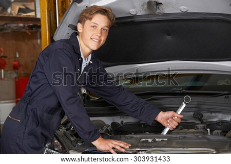 Apprentice Mechanic In Auto Shop Working On Car Engine - stock photo