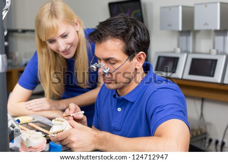 Apprentice watching dental technician applying porcelain to a dentition mold with a brush - stock photo