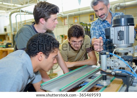 Apprentices learning to use machine - stock photo