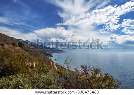 Approaching storm, waves splashing on huge rocks, off shore, along a rocky coastline, geological rock formations, traveling the Big Sur Highway (Highway 1), on the California Central Coast. - stock photo