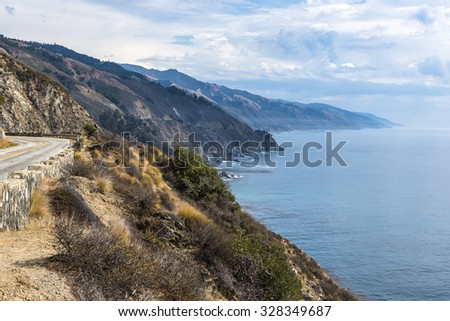 Approaching thunderstorm, waves splashing on huge rocks off shore, along a rocky coastline, with cloud covered mountain tops, traveling the Big Sur Highway (Highway 1) on the California Central Coast. - stock photo