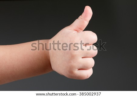 Approval thumbs up like sign, caucasian child hand gesture  over dark background - stock photo
